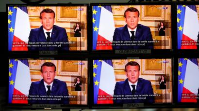 Emmanuel Macron is seen on four TV screens addressing the nation.