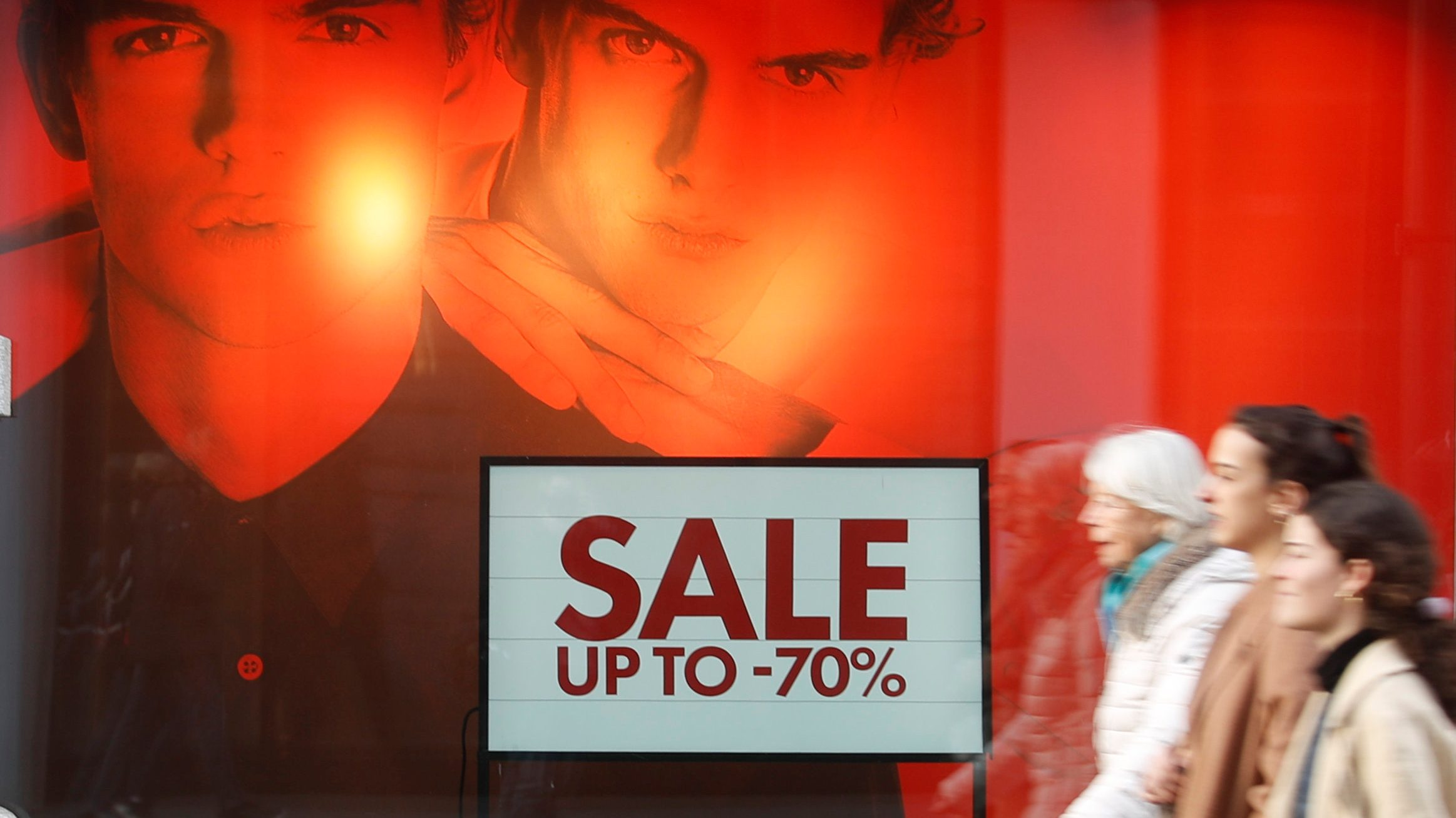 A sale is advertised in a fashion store's window display