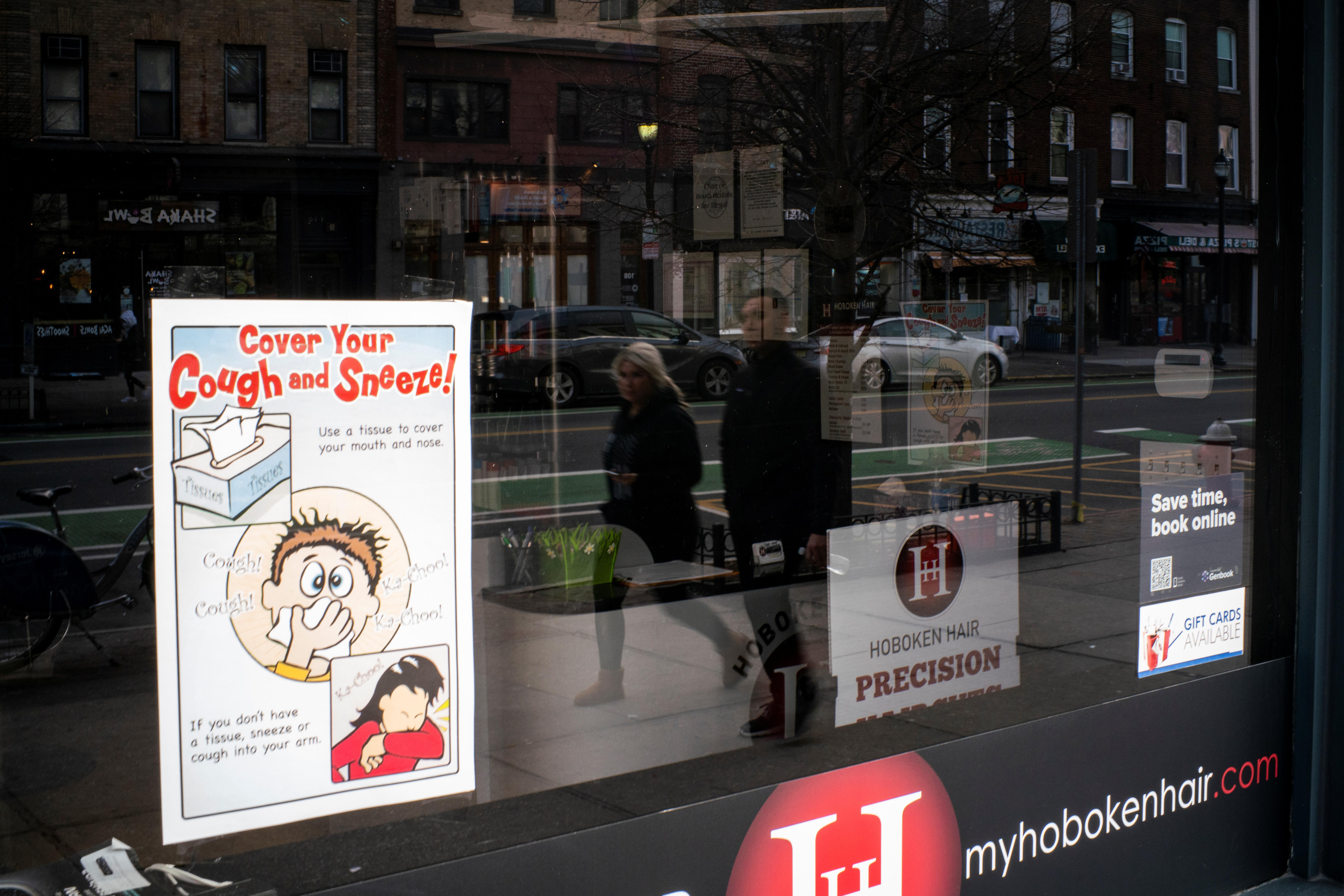 As pessoas refletem em uma vitrine de barbearia fechada devido ao surto de doença por coronavírus (COVID-19), em Hoboken, Nova Jersey