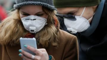 People wearing protective face masks use a smartphone