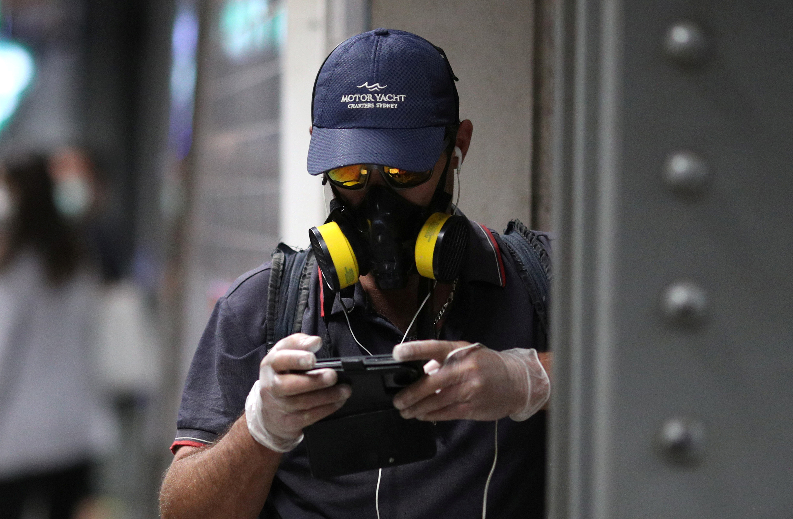 """A commuter wearing a gas mask uses his mobile device while standing at a train platform after New South Wales began shutting down non-essential businesses and moving toward harsh penalties to enforce self-isolation as the spread of coronavirus disease (COVID-19) reached a """"critical stage"""" in Sydney, Australia, March 24, 2020."""