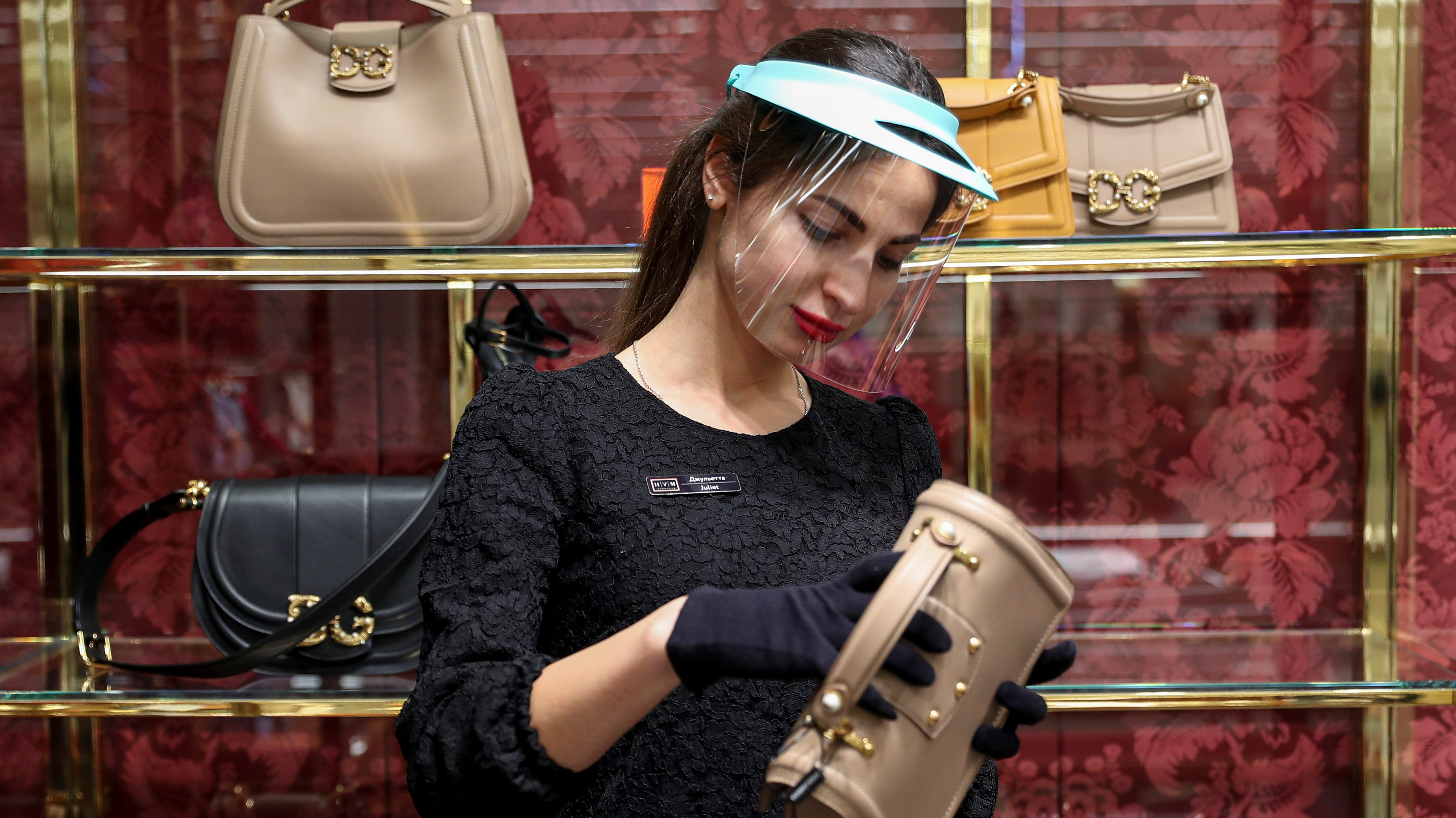 A shop assistant wearing a protective mask, used as a preventive measure against coronavirus disease (COVID-19), stands near a showcase with handbags