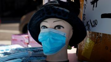 A mannequin is seen displayed with a surgical mask where a vendor was selling packages of surgical masks on a street corner in the Chelsea neighborhood of Manhattan