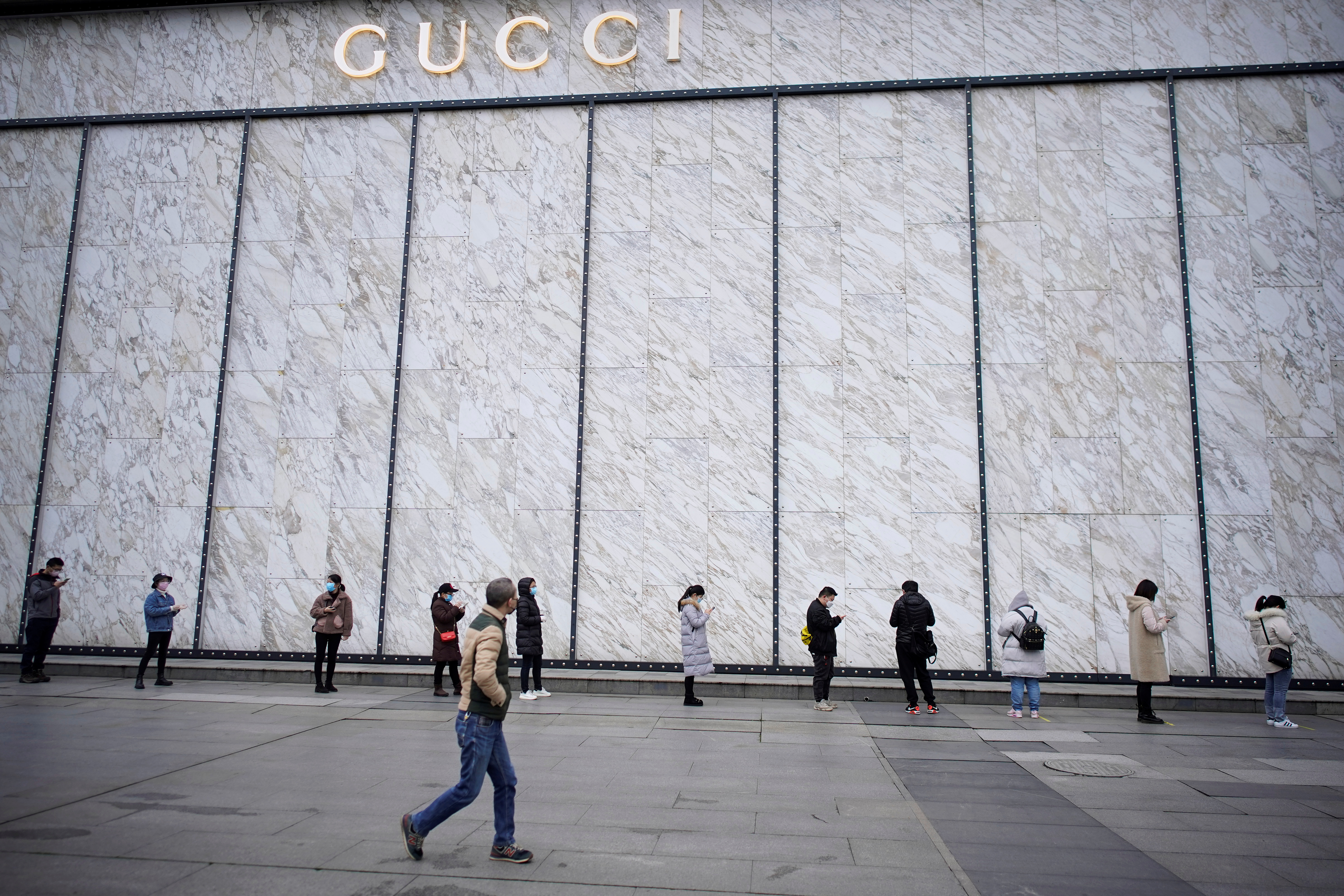 People wearing face masks line up to enter the shopping center outside the Gucci shop in Wuhan