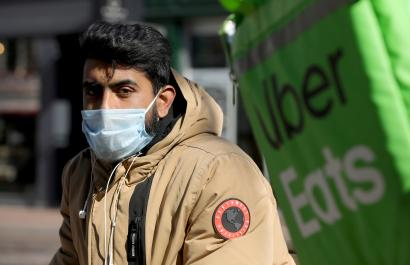 An Uber Eats food delivery courier wearing a protective face mask rides a bicycle as the spread of coronavirus disease (COVID-19) continues in Amsterdam, Netherlands