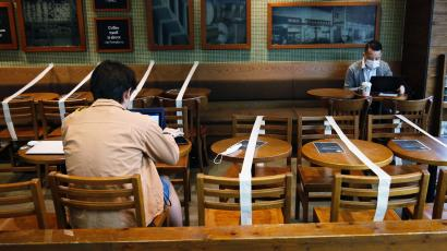 Two people sitting in a cafe. There is white tape separating their tables, sectioning off areas where customers can sit. Each of the people are wearing masks at their respective tables.