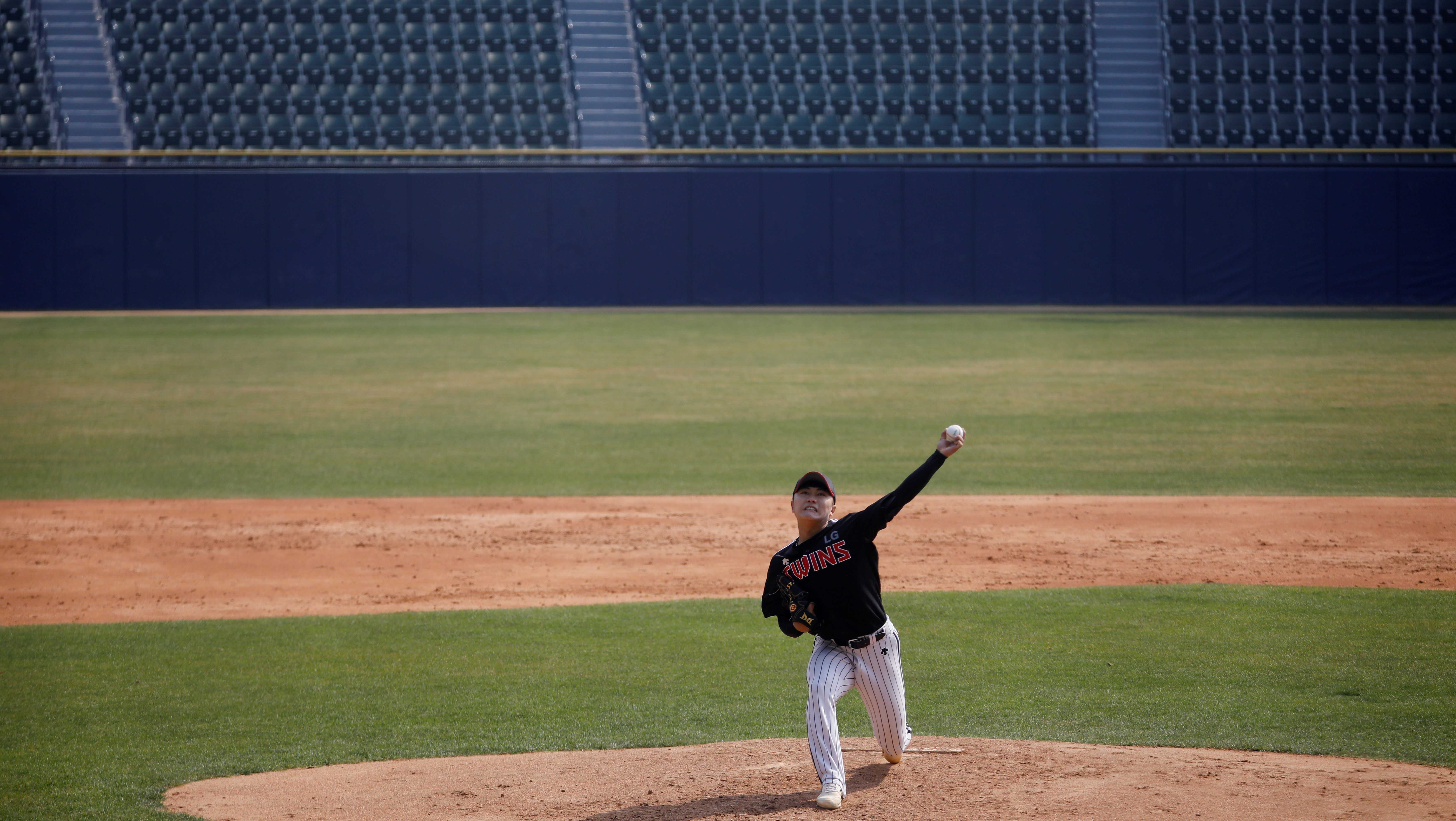 A baseball pitcher plays to an empty stadium during an online livestream