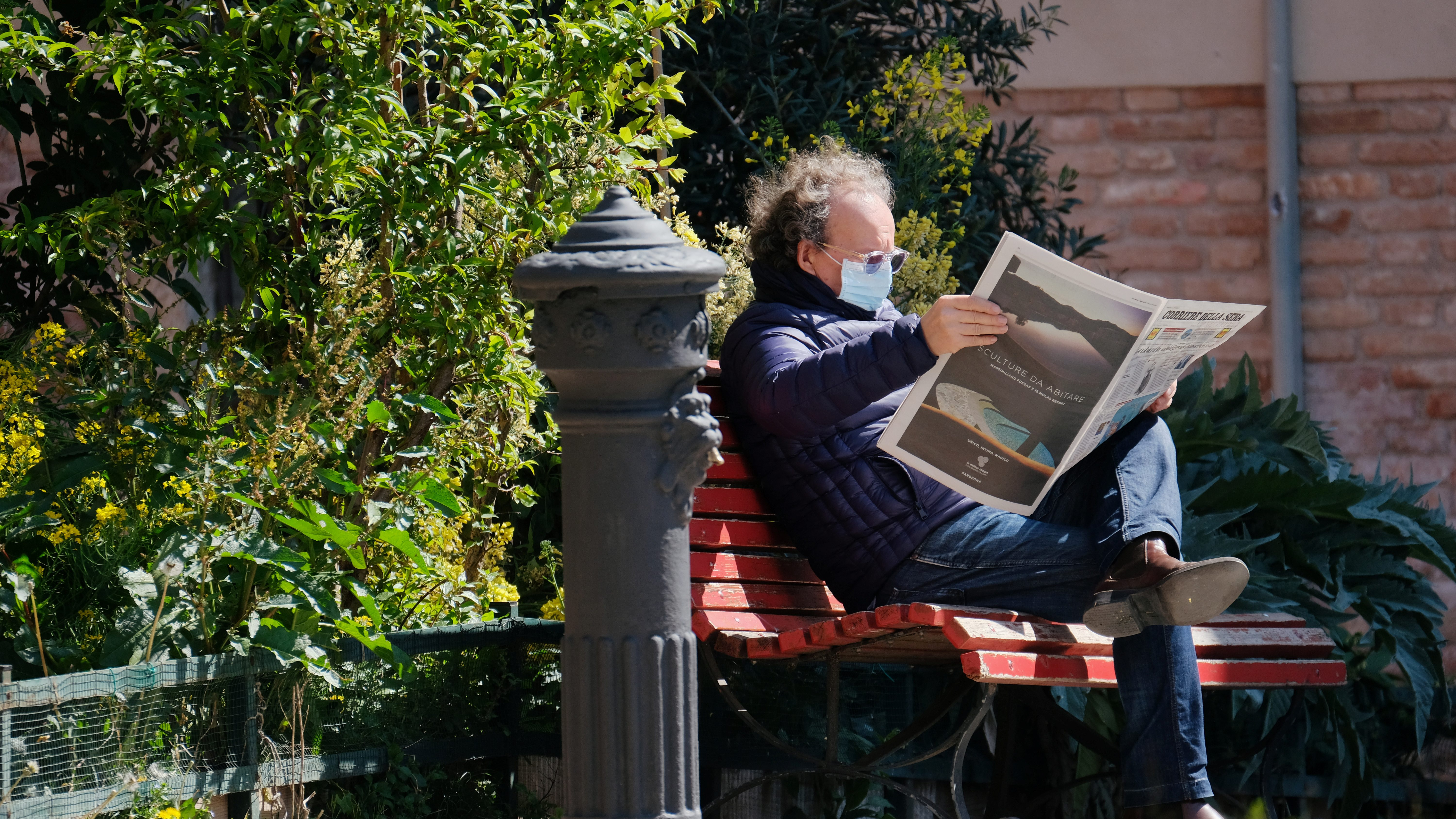 A man with a mask reads a newspaper outside.