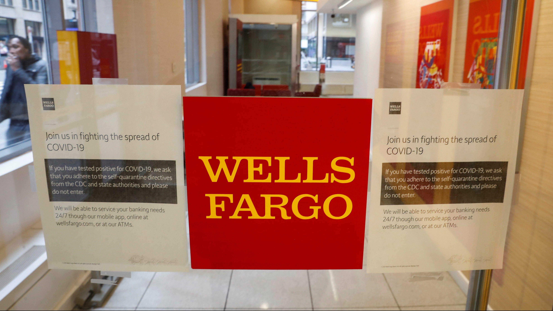 Warning signs for coronavirus disease (COVID-19) are seen on a Wells Fargo bank door in New York City.