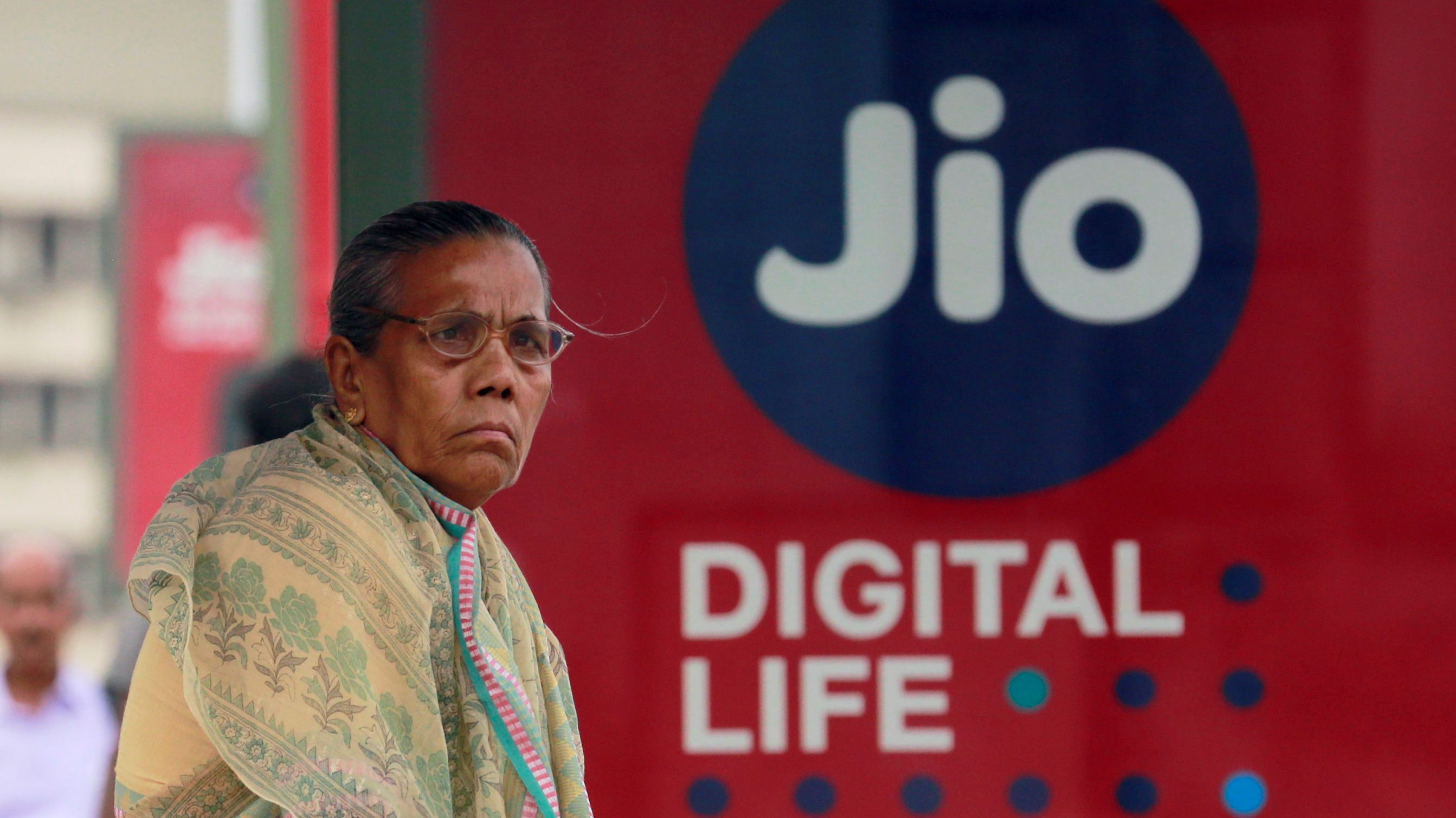 A woman waits at a bus stop with an advertisement of Reliance Industries' Jio telecoms unit in Mumbai
