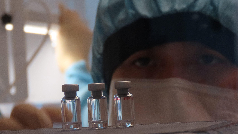 A scientist checks quality control of vaccine vials for correct volume at the Clinical Biomanufacturing Facility (CBF) in Oxford, Britain, April 2, 2020.