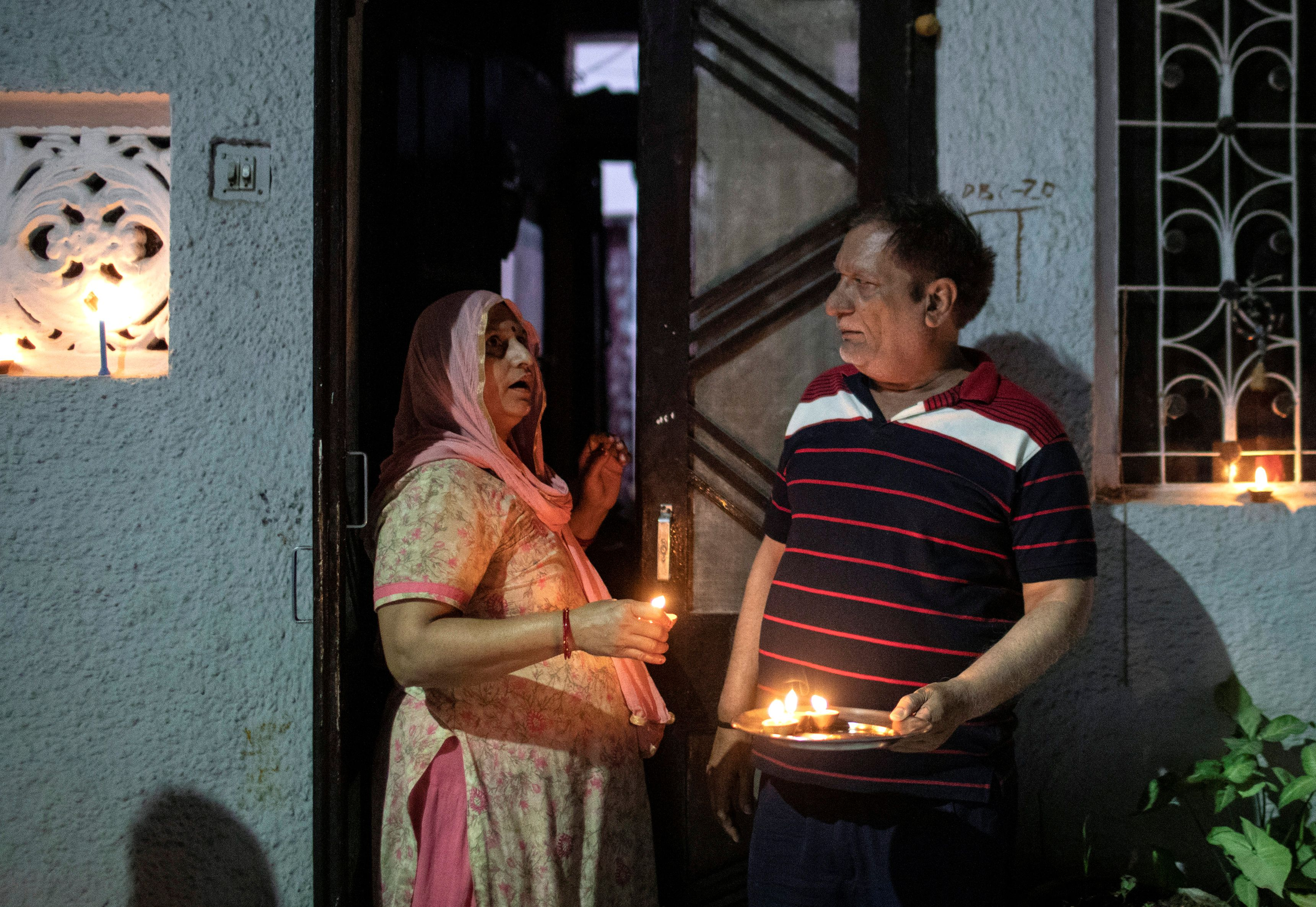 Residents stand with candles in their doorway in New Delhi.