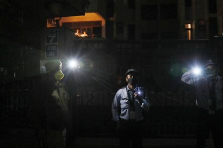Those on duty and with no access to candles improvised with flashlights on their mobile phones, like these security guards in New Delhi.