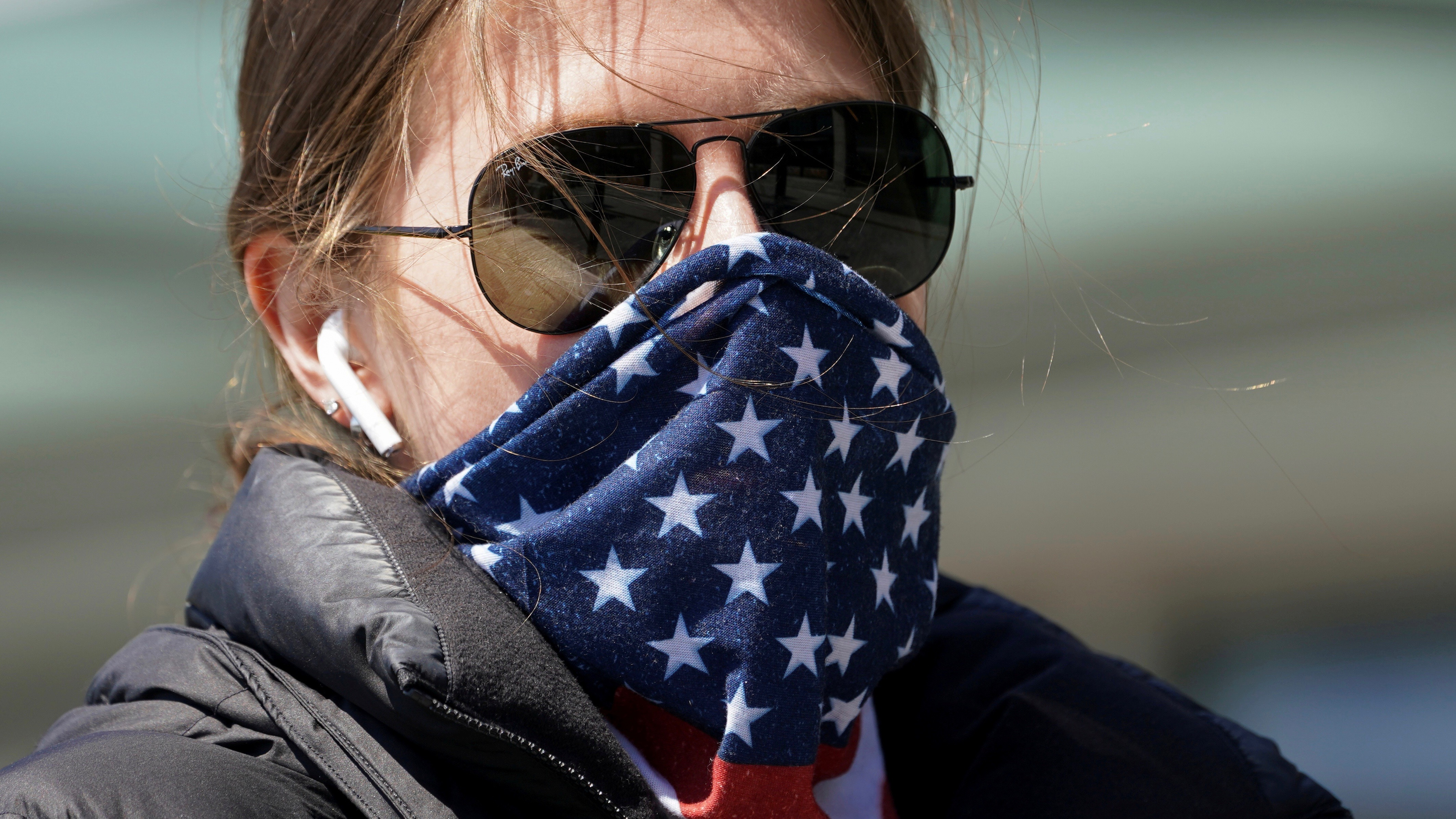 Woman with face covered by Stars and Stripes bandana.