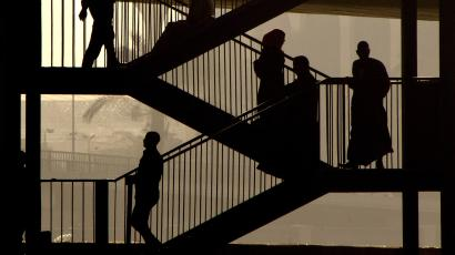 Egyptians walk down the stairs of a bridge in Cairo, Egypt.