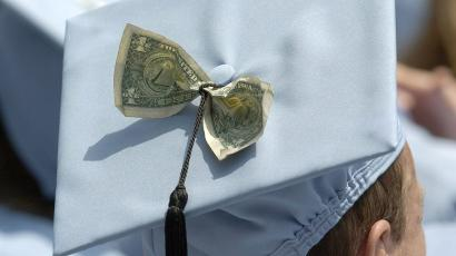 a mortarboard with a dollar bill tucked inside it