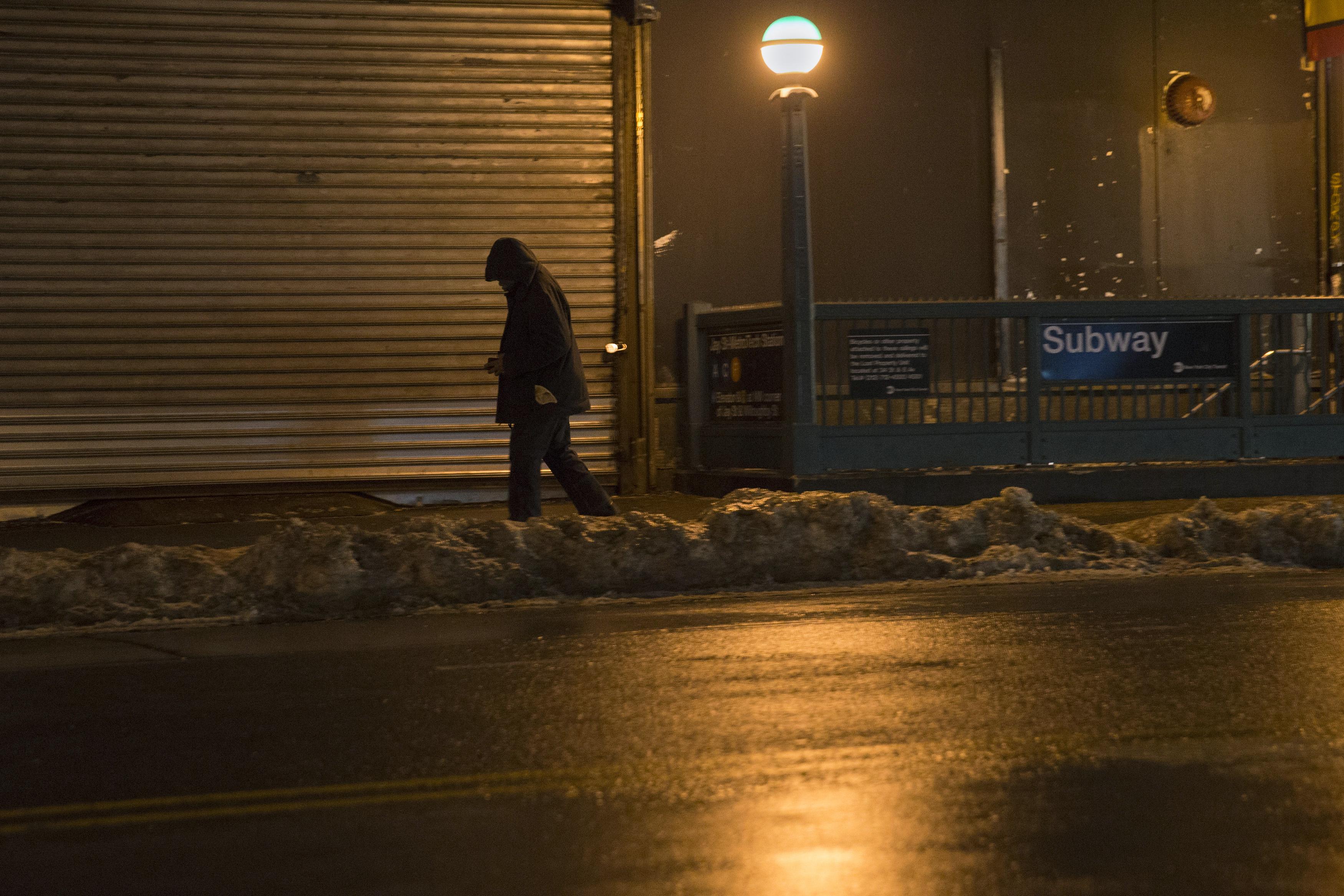 A man walks along the street in the Brooklyn borough of New York