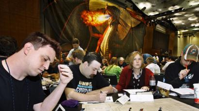 People sit around a table playing a game at a conference with a dragon in the background.