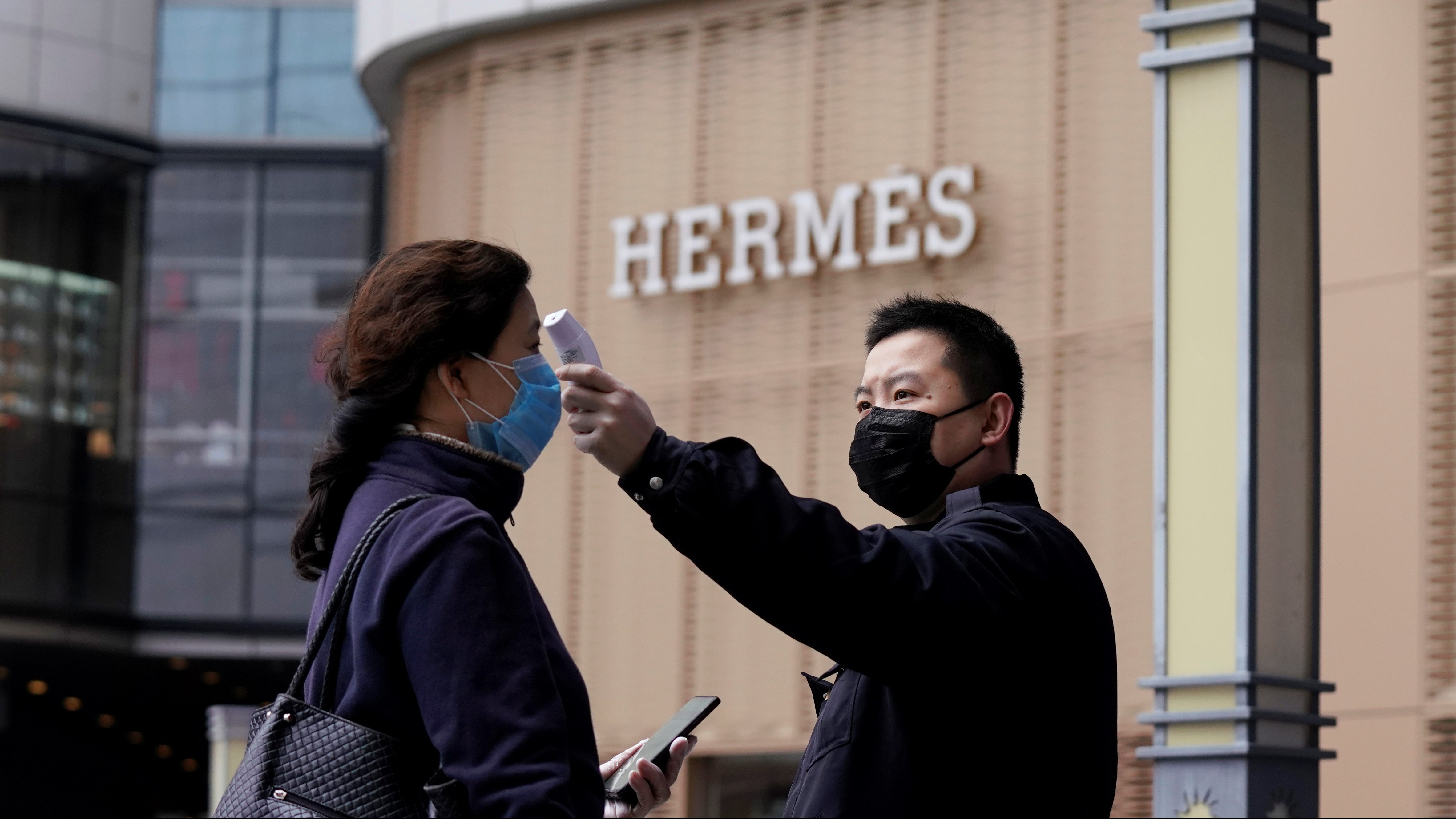 A management staff measures the body temperature of a woman entering a shopping mall near a Hermes store in Wuhan