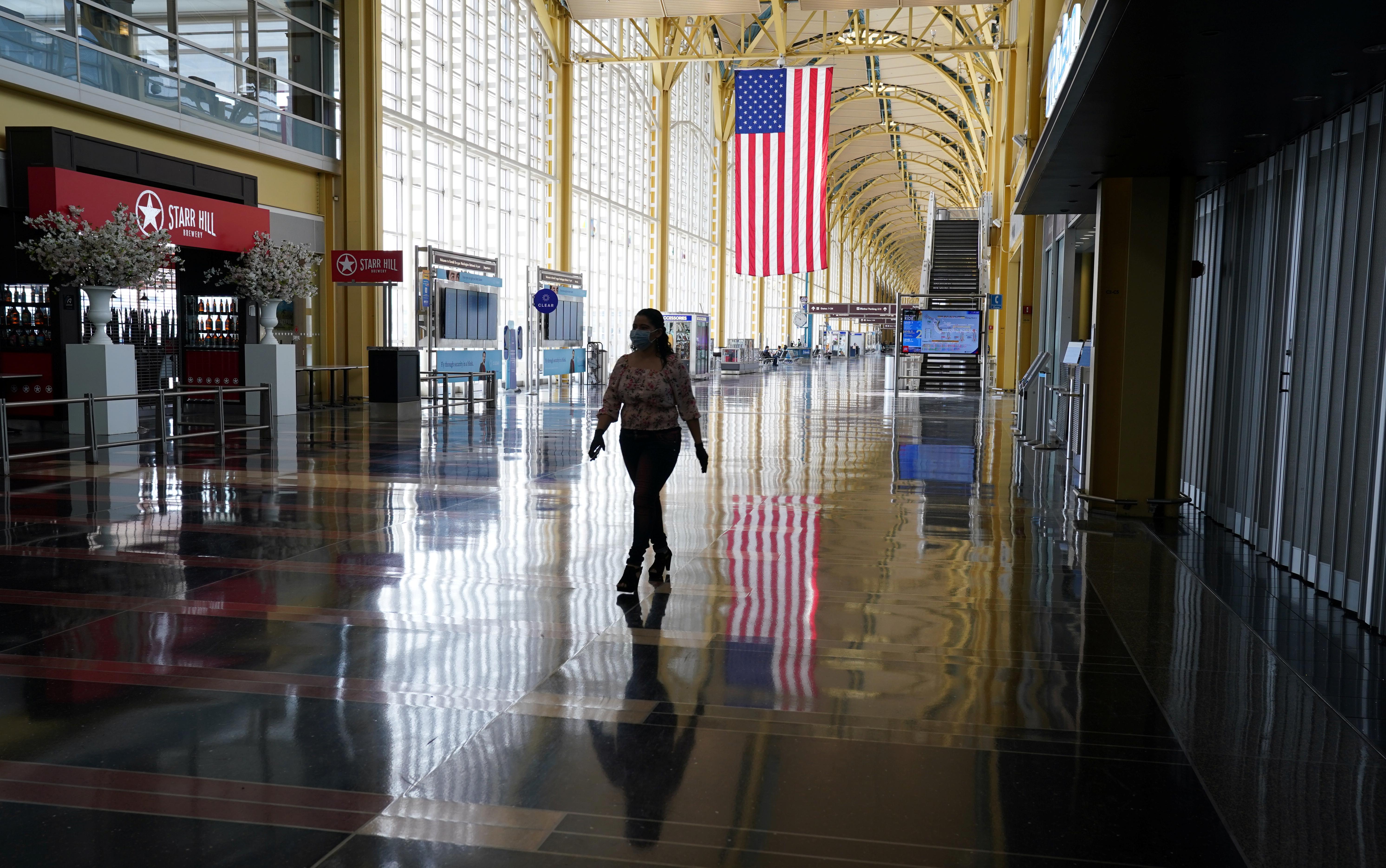Woman walks through mostly empty Reagan National airport in Washington