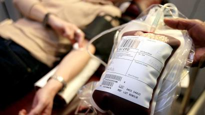A bag of blood in focus with an out of focus person in the background donating blood.