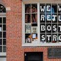 "A pedestrian walks past a sign in a shop window reading ""We Will Return Boston Strong"""