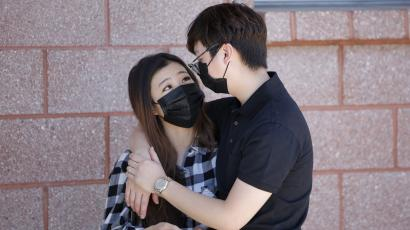 A man hugging a woman, both with masks on.