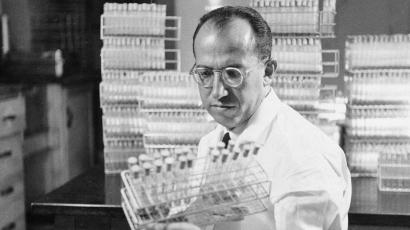A black and white grainy image of Dr. Jonas Salk looking at vaccine viles.