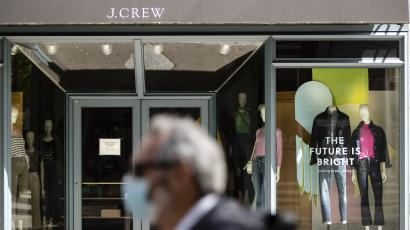 A person wearing a protective face mask as a precaution against the coronavirus walks past a shuttered J. Crew storefront in Philadelphi