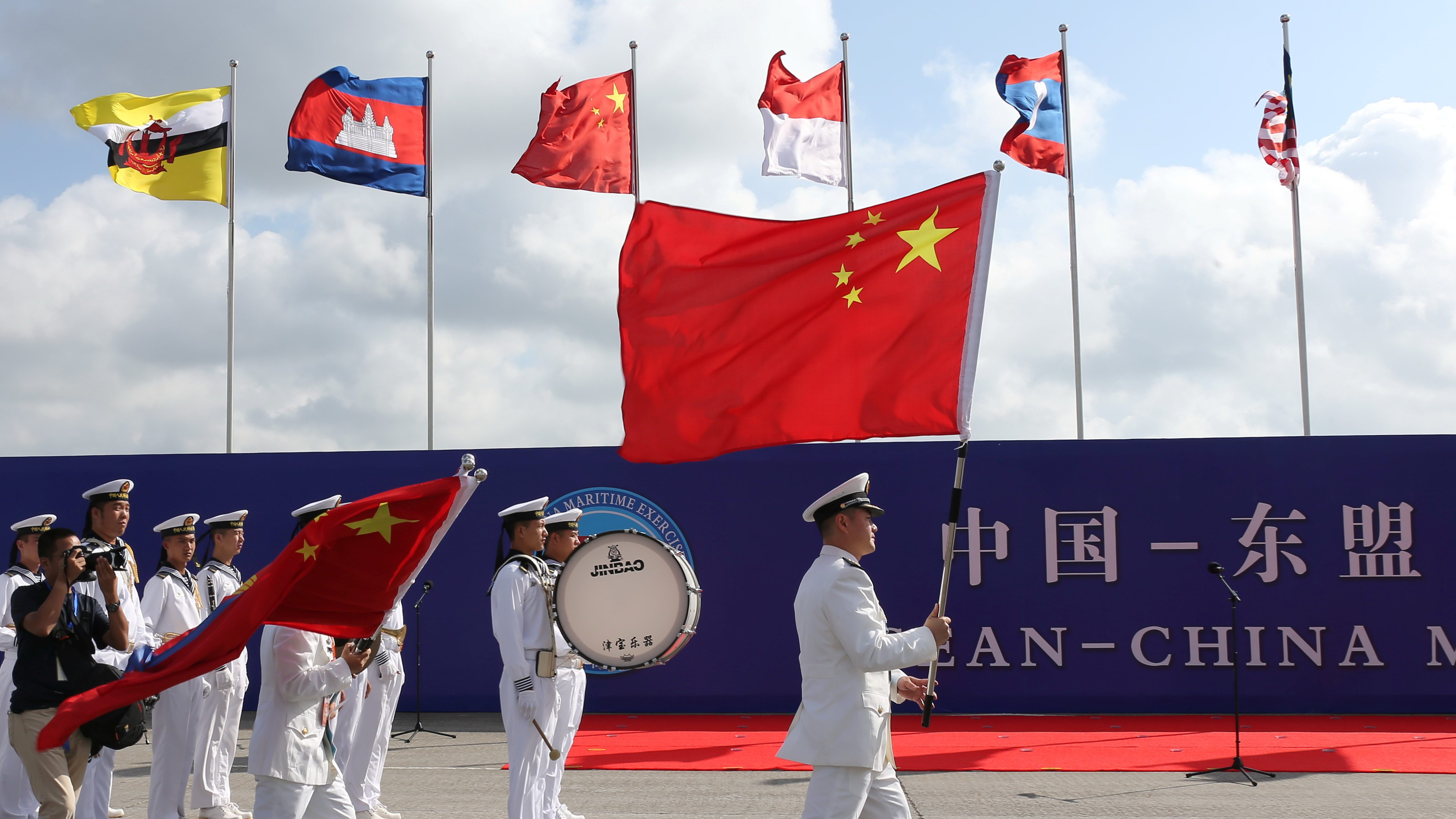 Members of the Chinese People's Liberation Army (PLA) and navy hold Chinese flags during the opening ceremony of the first China-ASEAN Maritime Exercise in Zhanjiang.