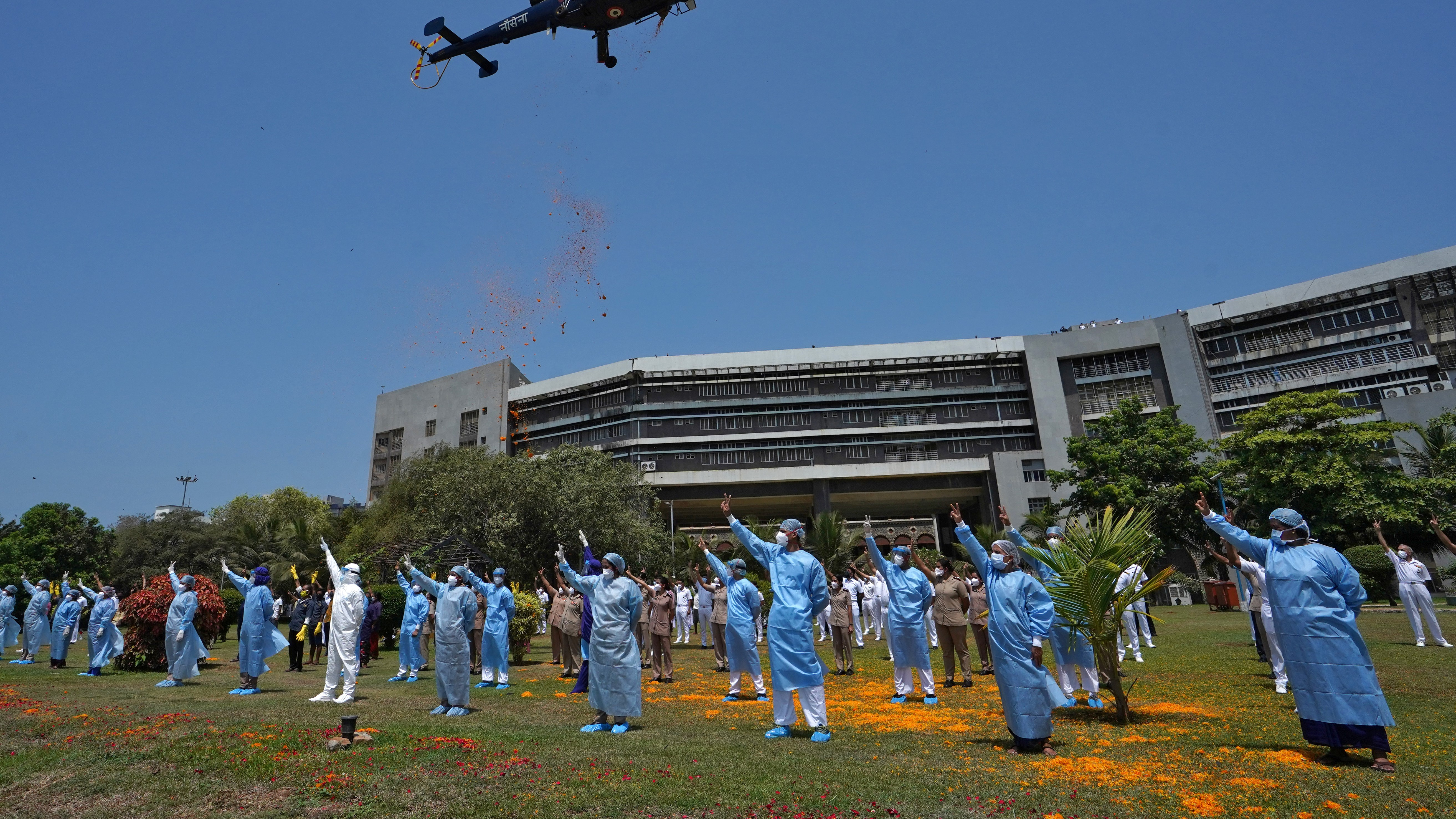 Indian Navy's Chetak helicopter drops flower petals on the staff of INHS Asvini hospital, Mumbai.