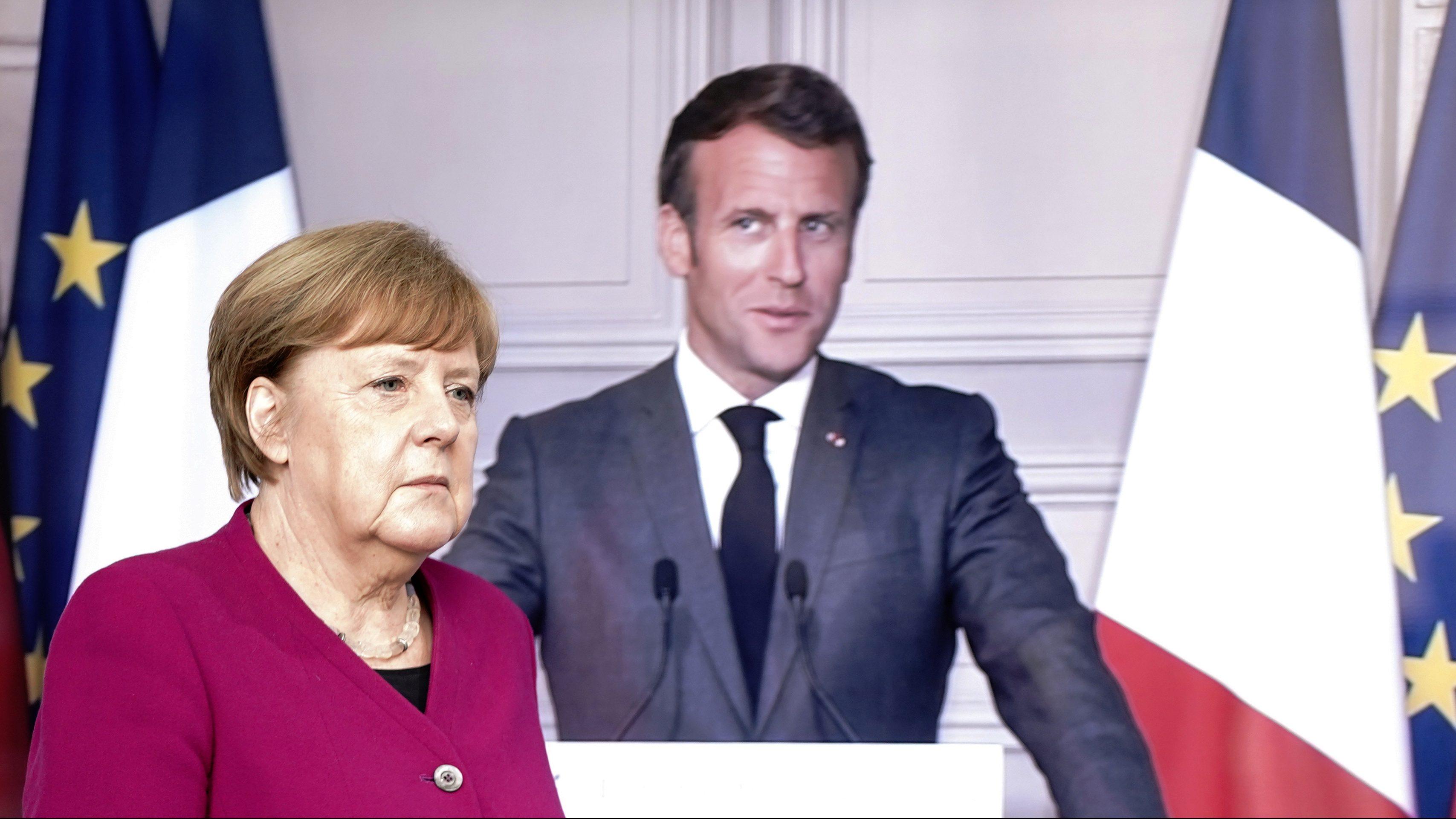 Angela Merkel walks by a television screen featuring Emmanuel Macron.
