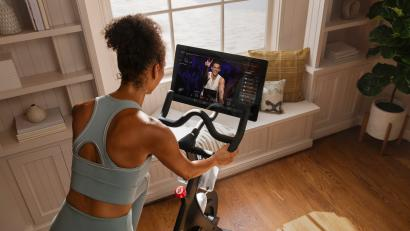 A woman at home on her Peloton stationary bike.