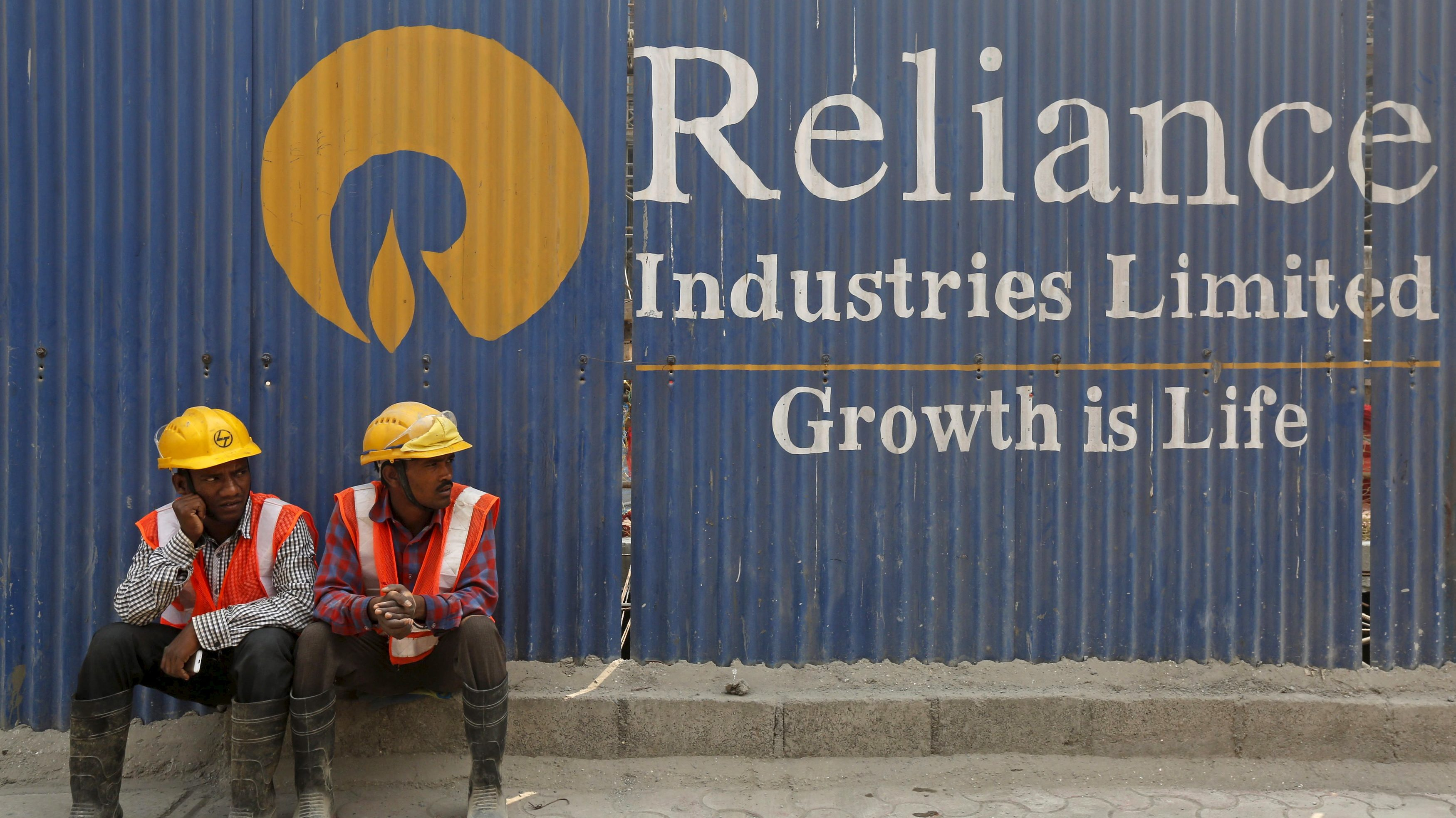 Labourers rest in front of an advertisement of Reliance Industries Limited at a construction site in Mumbai