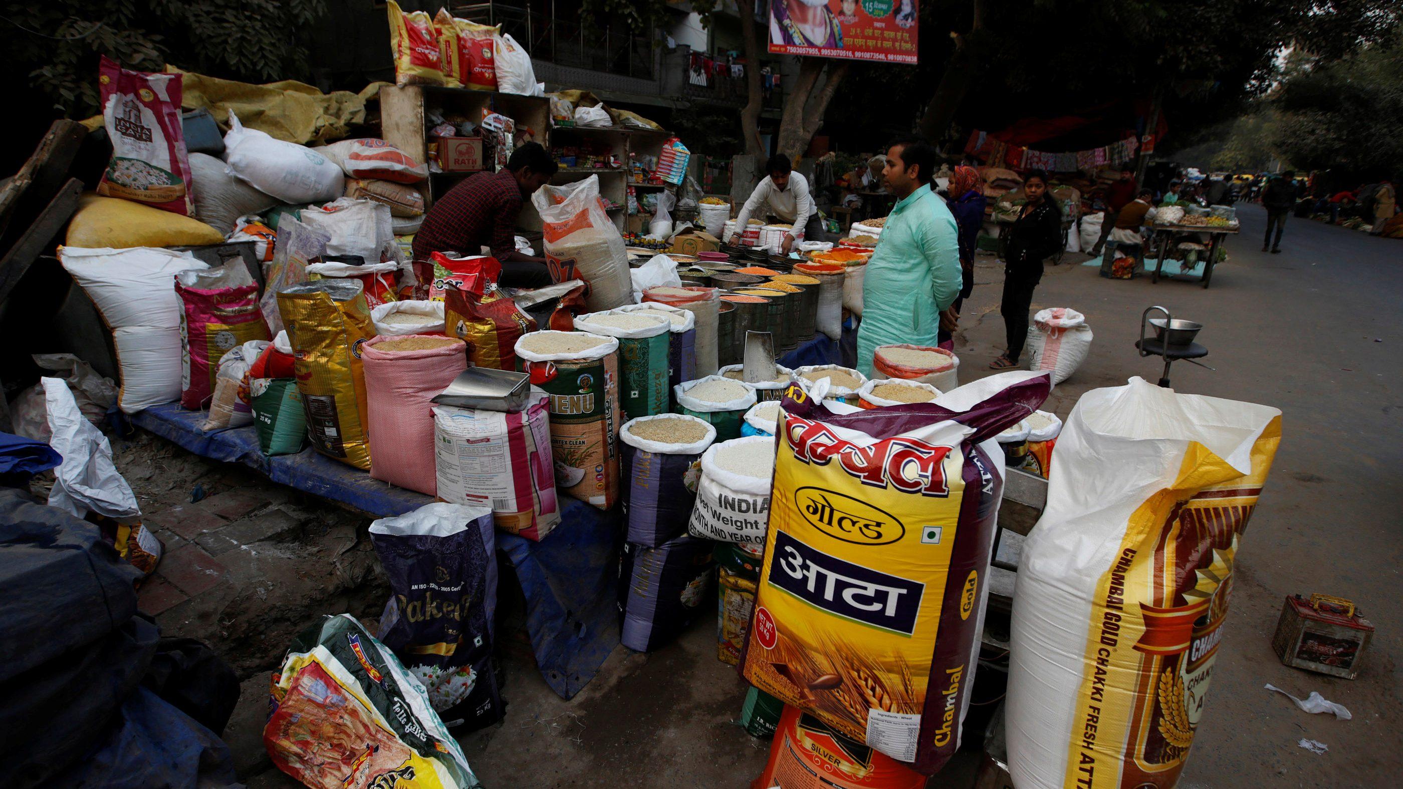 A vendor sells groceries to a customer at his roadside shop in New Delhi