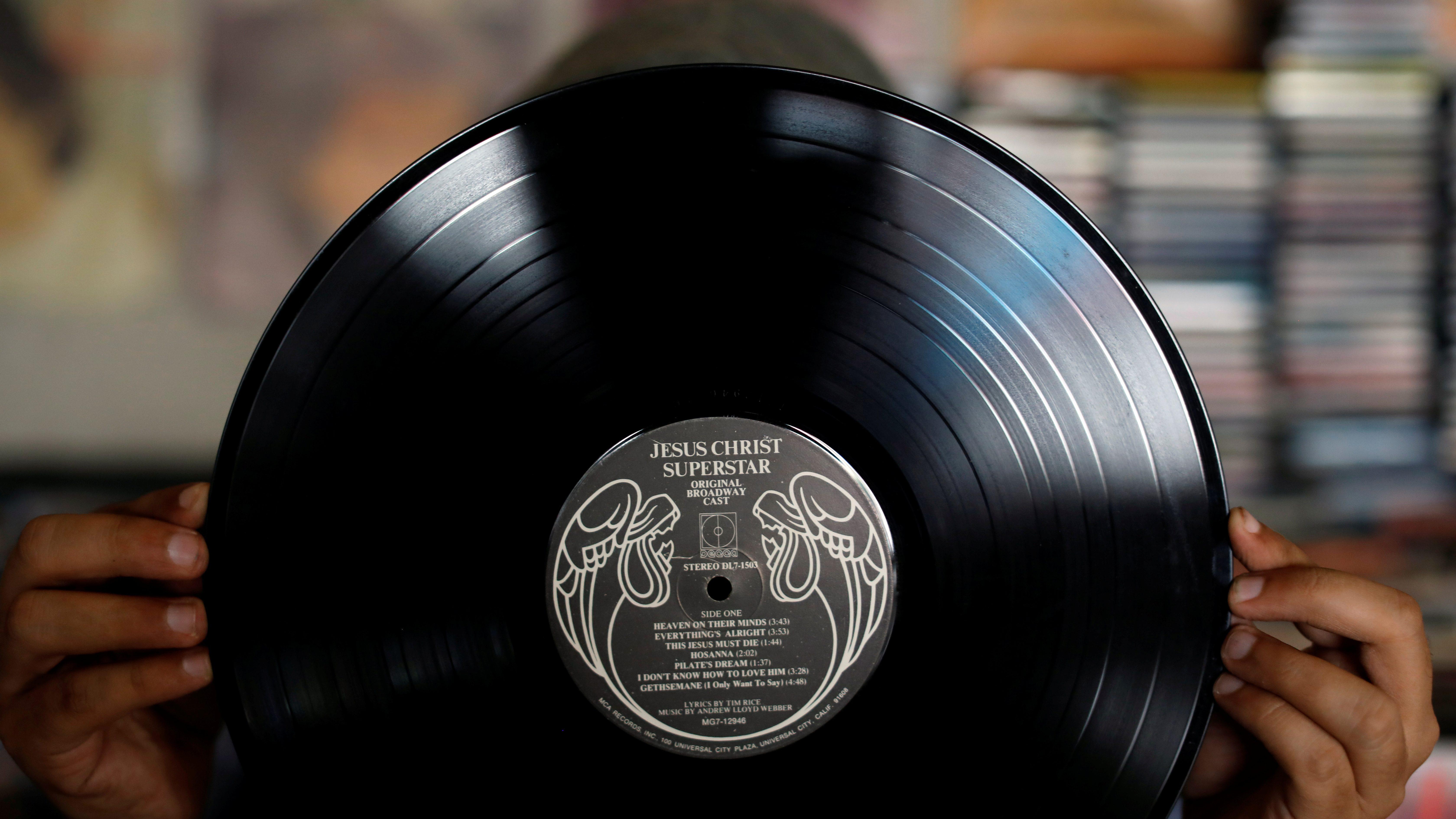 "A man shows a vinyl record at ""El Pollo Musical"" (The Musical Chicken) record store in San Salvador"