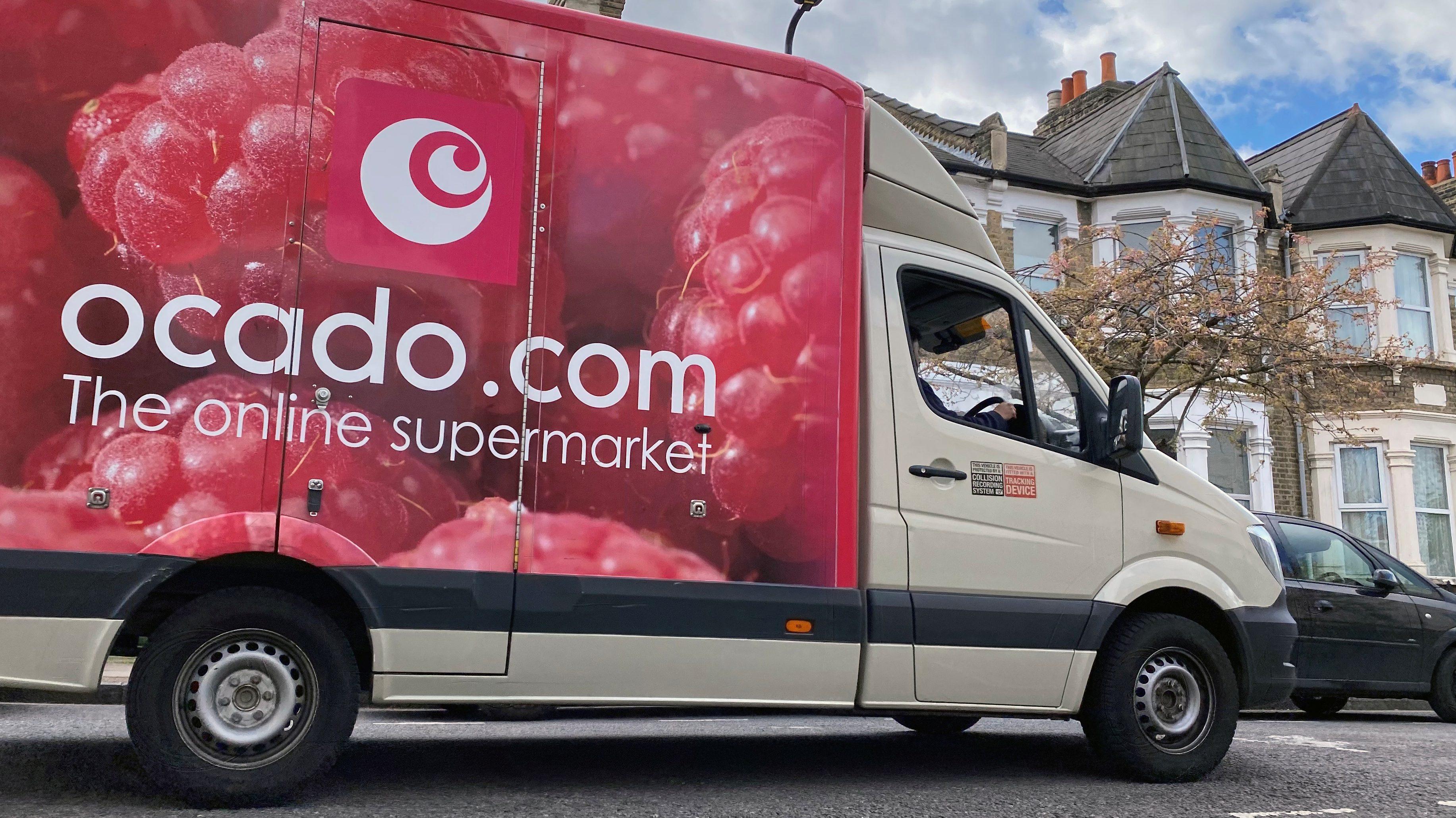An Ocado delivery van drives down a London street.