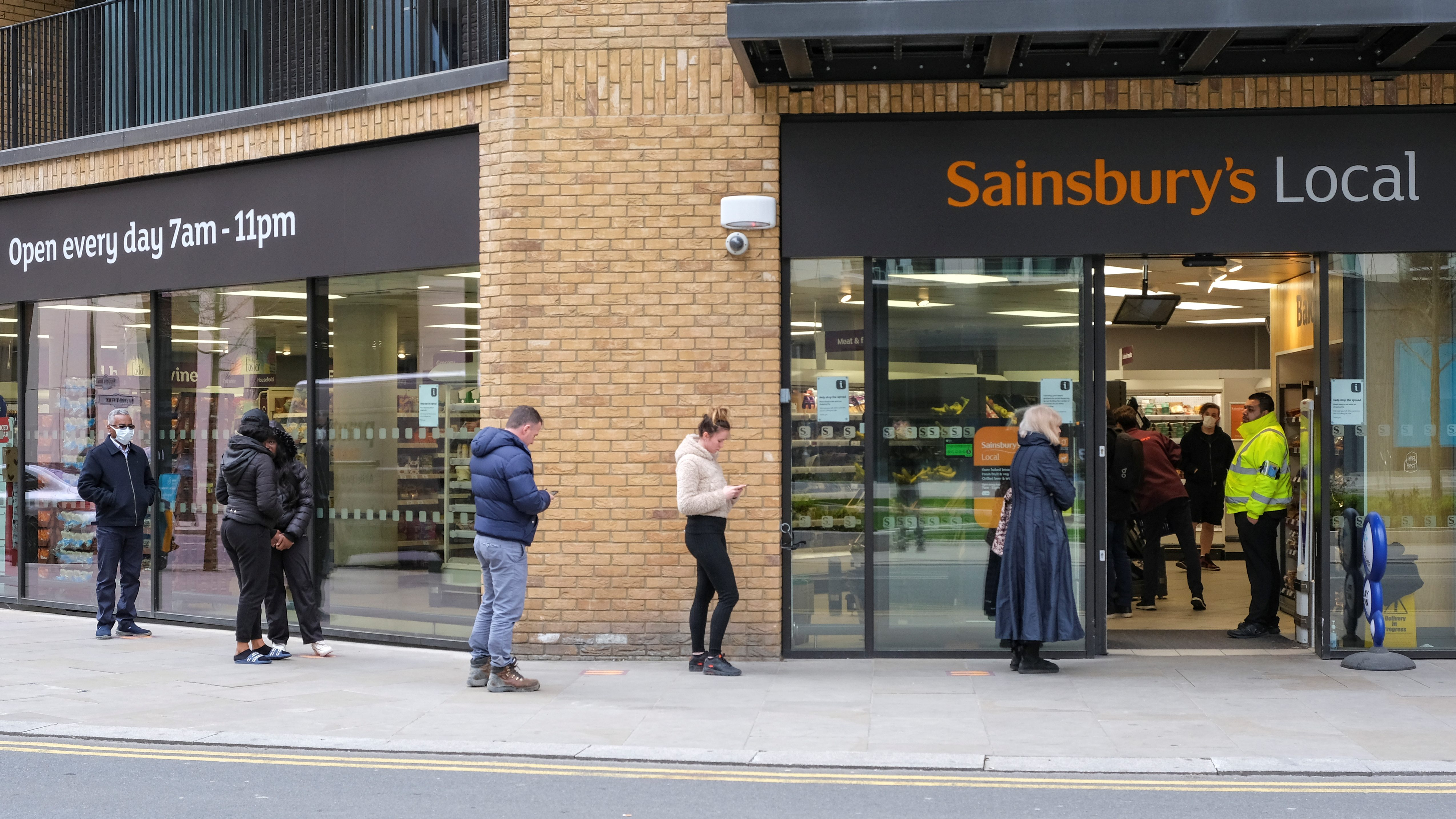 People wait in line to shop at a Sainbury's Local in London.
