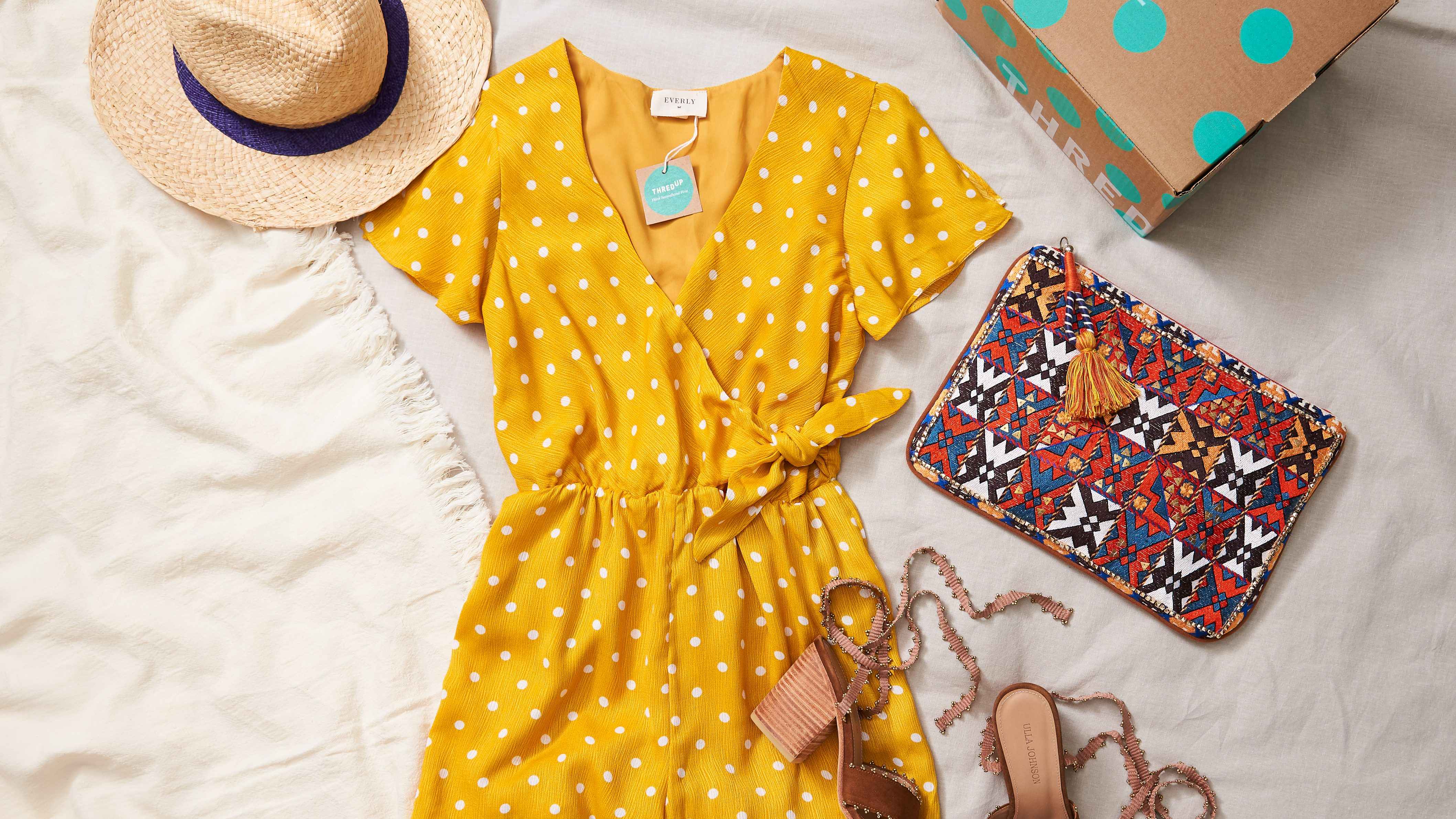 A yellow dress and accessories such as a bag and clothes lie flat on a bed