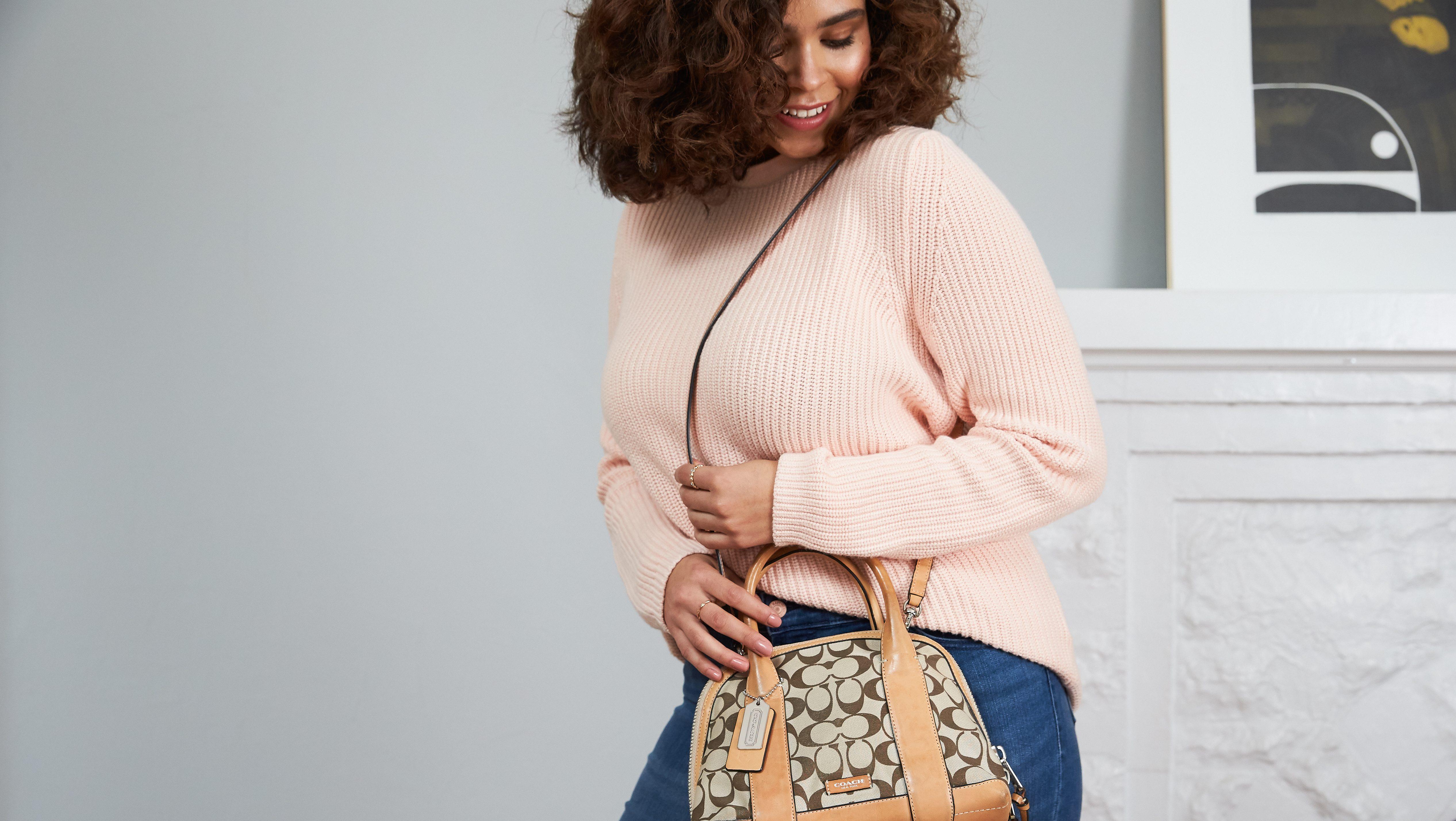 A woman wears a Coach bag