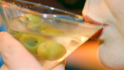 a woman sips a martini with olives in it