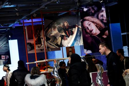 Shoppers walk past images of pop star Beyonce at an Adidas store