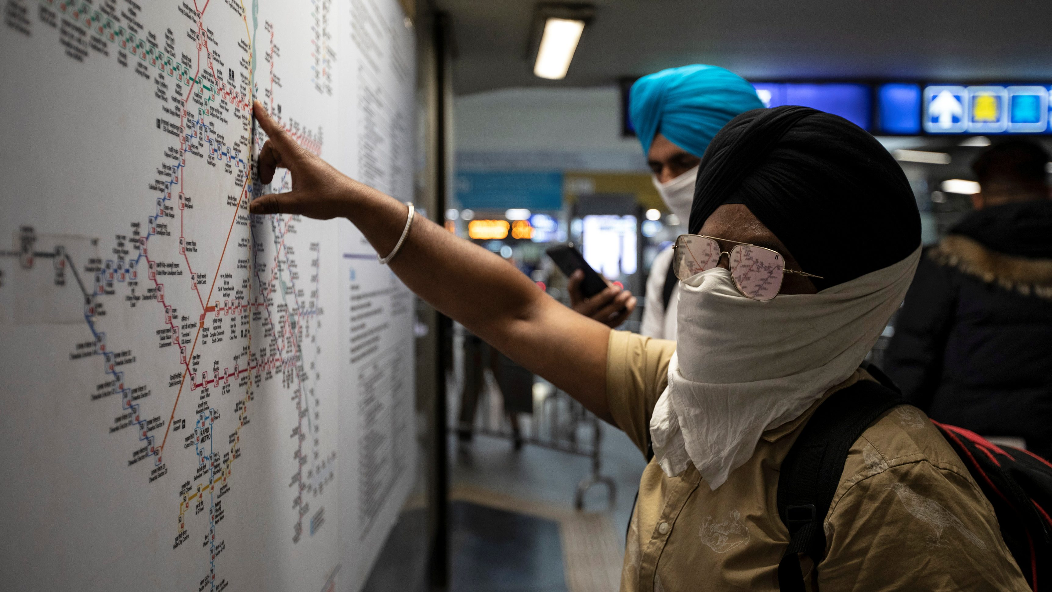 Commuters wearing handkerchiefs as masks look at a metro train map at a station, amid coronavirus disease (COVID-19) fears, in New Delhi, India, March 13, 2020. REUTERS/Danish Siddiqui