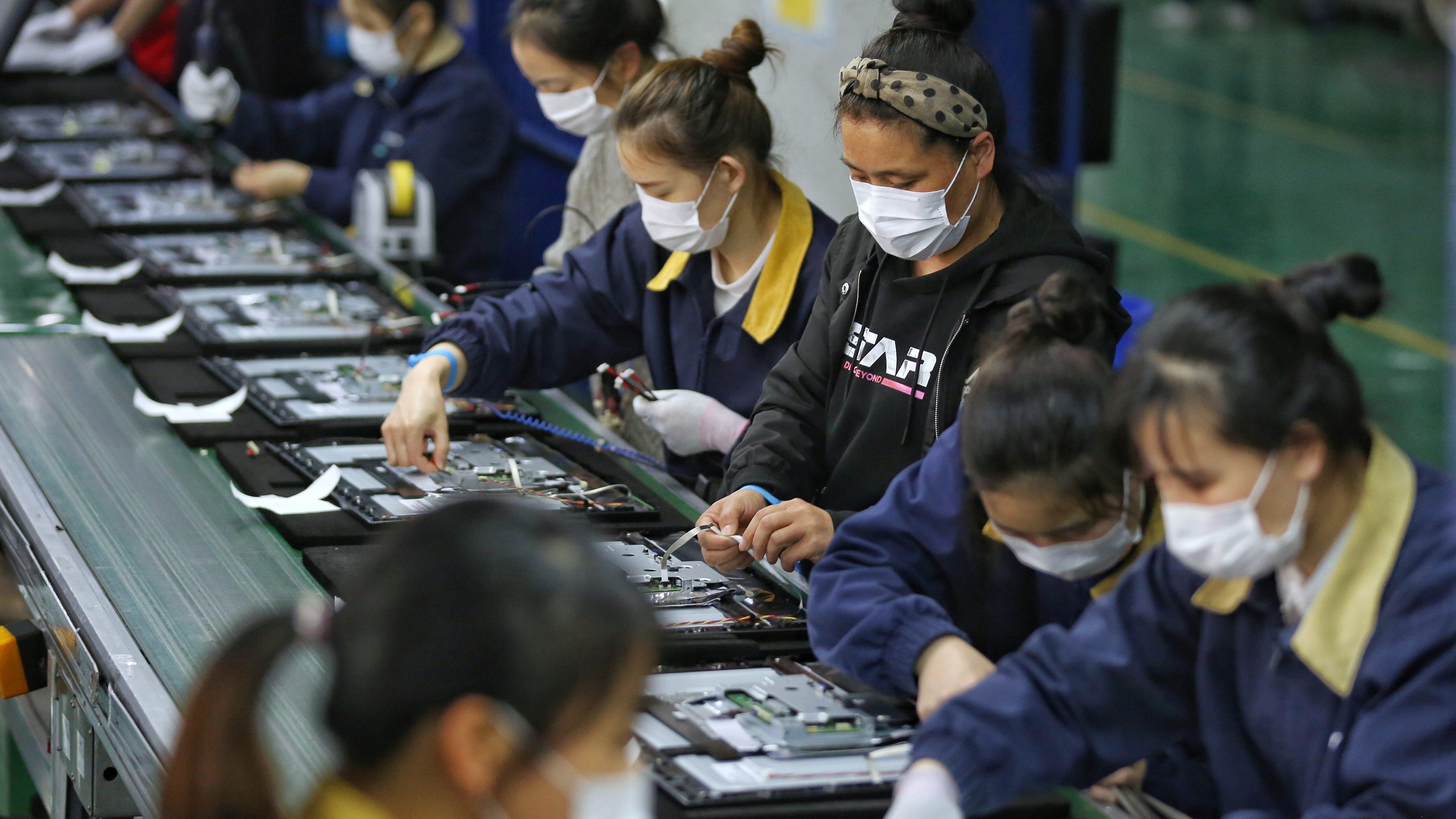 Employees, wearing masks, work on a production line manufacturing display monitors at a TPV factory in Wuhan