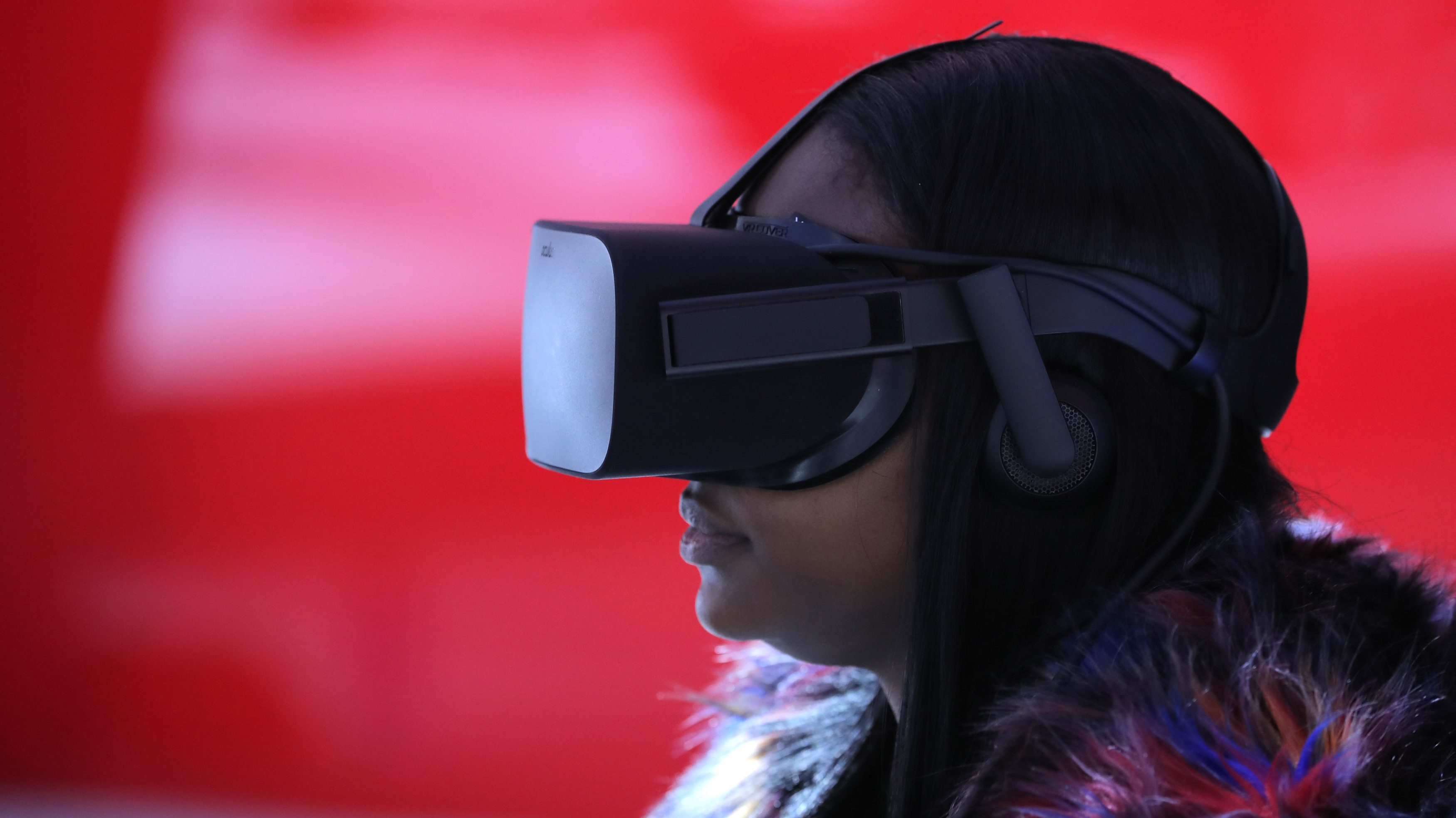 A woman wears VR goggles as she sits in a virtual reality booth.