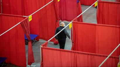Red curtains make makeshift rooms in a large stadium. The beds are blue, and a single man with a mask on walks in between rows of curtains.