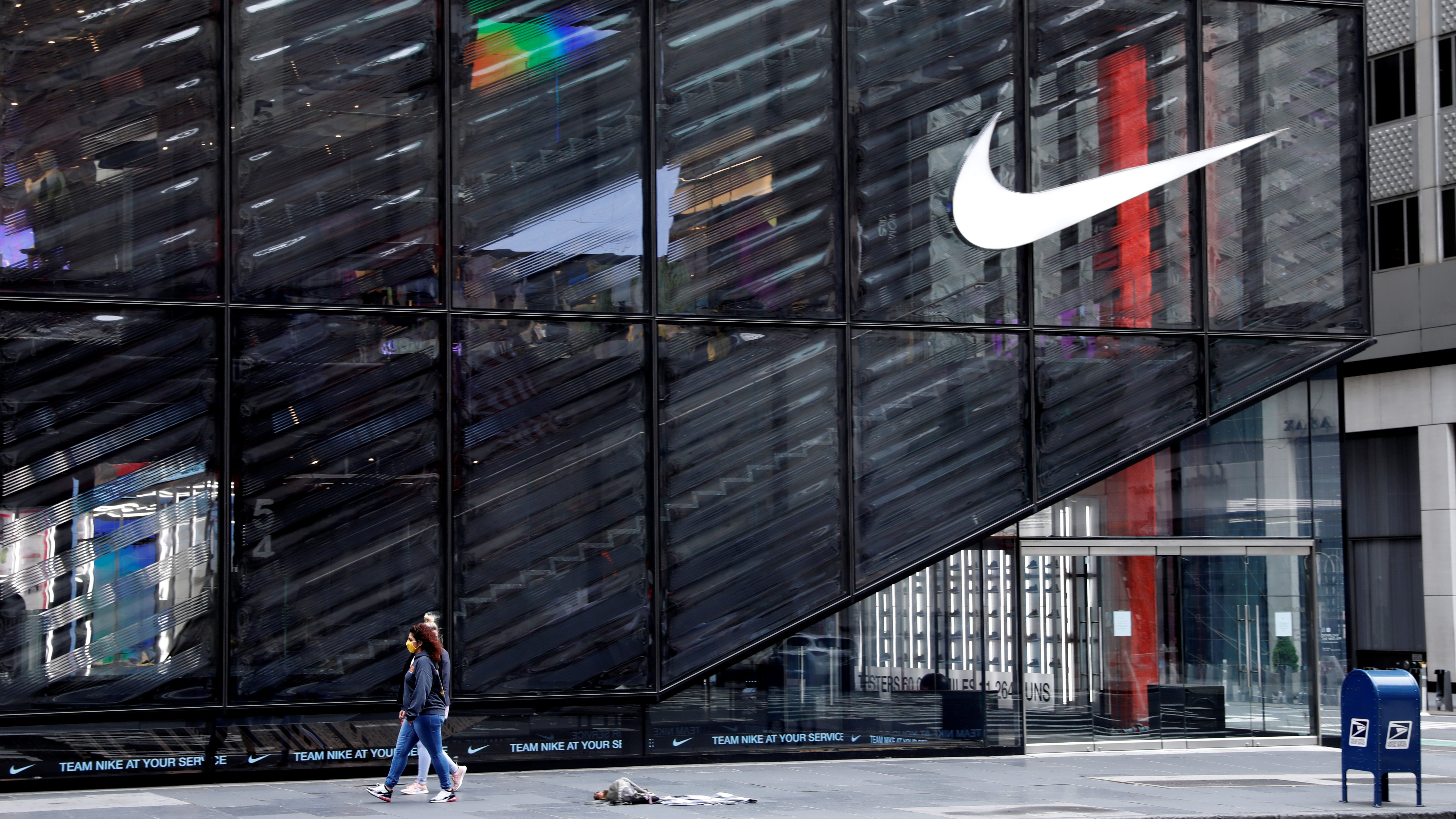 People wearing protective face masks walk past the closed Nike store on a nearly empty 5th Avenue
