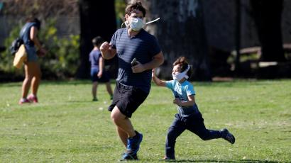 A young boy wearing a mask chases an older man wearing a mask.
