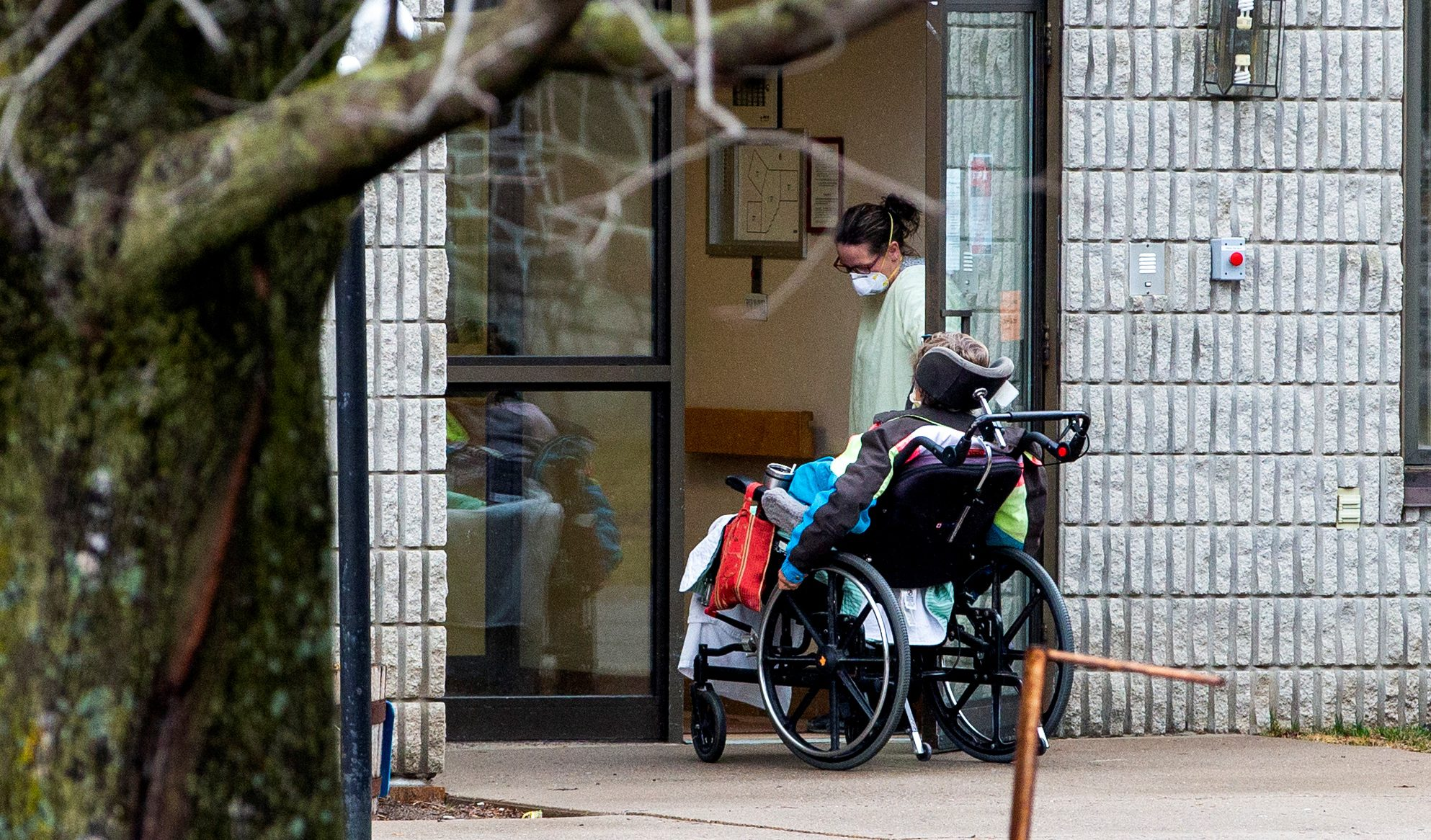 FILE PHOTO: A woman opens the door to a person in a wheelchair at Pinecrest Nursing Home after several residents died and dozens of staff were sickened due to coronavirus disease (COVID-19), in Bobcaygeon, Ontario, Canada March 30, 2020.