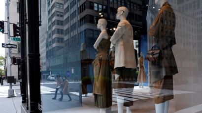 People wearing protective face masks are seen reflected in the windows of the closed Saks Fifth Avenue store on 5th Avenue, during the outbreak of the coronavirus disease (COVID-19) in Manhattan
